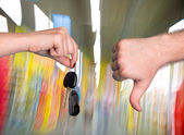 Woman holding car key, man showing thumb down — Stock Photo