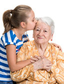 Granddaughter kissing her old grandmother  — Stock Photo