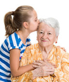 Granddaughter kissing her old grandmother — Stockfoto