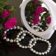 Pearl bracelets, bouquet of roses and a mirror — Stock Photo