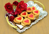 Heart-shaped cookies and roses on a metal tray — Stock Photo