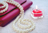 Res candle, handbag and pearl — Stock Photo