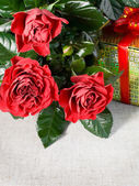 Three red roses and gift — Stockfoto