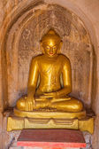 Old renovated sculpture of a golden seated Buddha — Stock Photo
