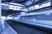 Railway station with train in movement. — Stock Photo