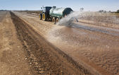 Tractor spreading water — Stock Photo