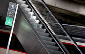 Signpost and escalators in a railway station — Stock Photo