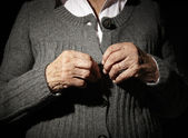 Old hands buttoning — Stock Photo