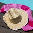 Sun hat and beach towel by swimming pool — Stock Photo