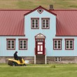 Traditional icelandic metallic house. Man in a lawn mower. — Foto de Stock