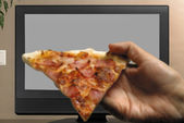 Man hand with pizza slice watching TV — Stock Photo