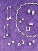 Collection of silver jewelry on purple background tone — Stock Photo