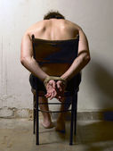 Tortured man on a chair with tied hands — Stock Photo