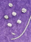 Silver jewlelry still life with purple background — Stock Photo