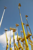 Yellow telescopic cranes under a blue sky — Stock Photo