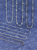 Silver necklaces over a blue background — Photo