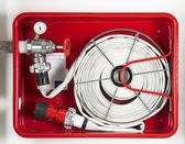 Fire hose equipment in a red metallic box — Stockfoto
