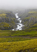 Iceland landscape in the east fiords. River and rocks with fog. — Stock Photo