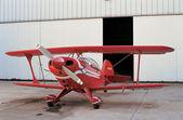 Avión rojo y un hangar en el aeródromo — Foto de Stock