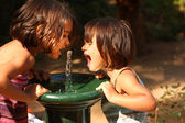 Two little girls smiling and playing outdoors — Stock Photo