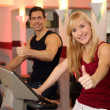 Attractive woman and a man cycling in a gym — Stock Photo