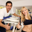 Attractive blonde woman and her trainer in a gym — Stock Photo