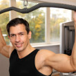 Handsome man working out in a gym — Stock Photo