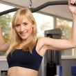 Attractive blonde woman weightlifting in a gym — Stok fotoğraf