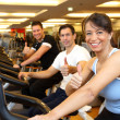 Two man and a woman on exercise bike showing thumbs up — Stock Photo