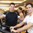 Three friends on exercise bikes in a gym - Stock Photo