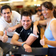 Royalty-Free Stock Photo: Group of three friends on treadmill giving thumbs up