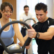 Personal trainer explaining vibration plate in gym to fema — Stock Photo #17591337