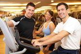 Three friends on exercise bikes in a gym — Stock Photo