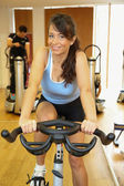 Woman on exercising bike smiling — Foto Stock