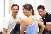 Group of three friends on treadmill smiling — Stock Photo