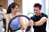 Personal trainer explaining a vibration plate in a gym to a fema — Stock Photo
