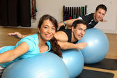 Two men and one woman exercising on gymnastics balls — Stock Photo