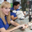 Stock Photo: Techniciworking on dental prosthesis under microscope