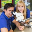 Dental technicians working on microscope - Stock Photo