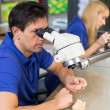 Dental technicians with microscope at work - Stock Photo