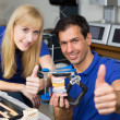 Two dental technicians with articulator showing thumbs up — Stock Photo #18767403