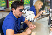 Dental technicians with microscope at work — Stock Photo