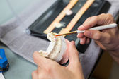 Closeup of dental technician applying porcelain — Stock Photo