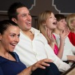 Laughing audience at the movies — Stockfoto