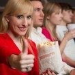 Woman in movie theatre showing thumbs up — Stock Photo