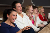 Laughing audience at the movies — Stock Photo