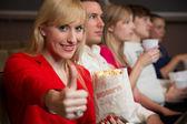 Kobieta w kino przedstawienie kciuki w górze — Zdjęcie stockowe