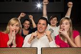Audience in cinema cheering — Stock Photo
