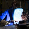 Worker with welding helmet welds steel — Stockfoto