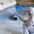 Stock Photo: Vehicle painter spraying color on construction bucket